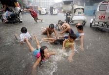 Филиппинские дети играют на улице во время ливня
